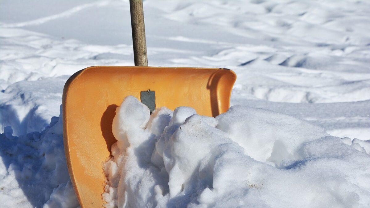 Skotta snö utanför tomten